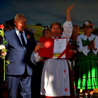 Na fotografii Marszałek Województwa Warmińsko-Mazurskiego - Gustaw Marek Brzezin oraz przedstawicielka zwycięzców I miejsca w konkursie na najładniejszy wieniec dożynkowy.