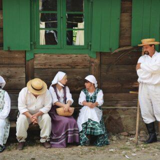 Na zdjęciu znajduje się 5 osób w strojach ludowych w czasie przygotowania do żniw.