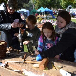 Dzieci uczestniczące w warsztatach robienia drewnianych bąków