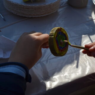 Ręce dziecka malujące drewnianego bączka